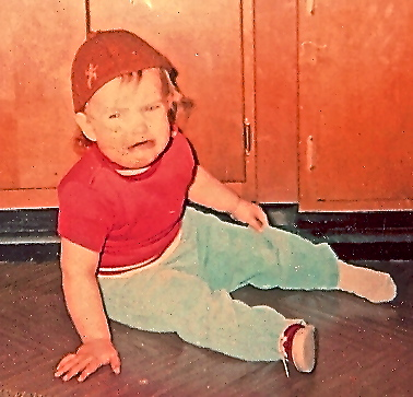 Toddler with brownie hat crying on floor.