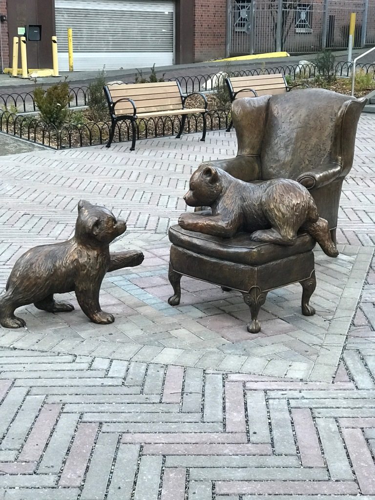 Statue of two bear cubs playing on wingback chair and ottoman in park setting.