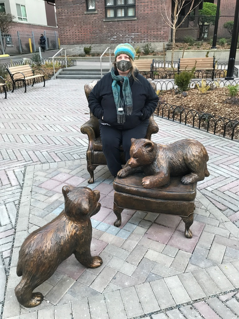Women with mask sitting in bronze chair of statue with bronze bear cubs in small park.