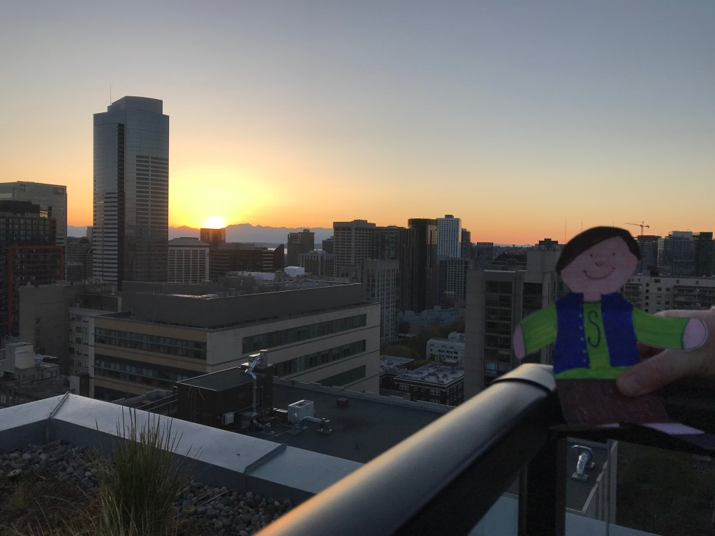 Paper cut out of boy on high rise roof deck with city and sunset behind him.