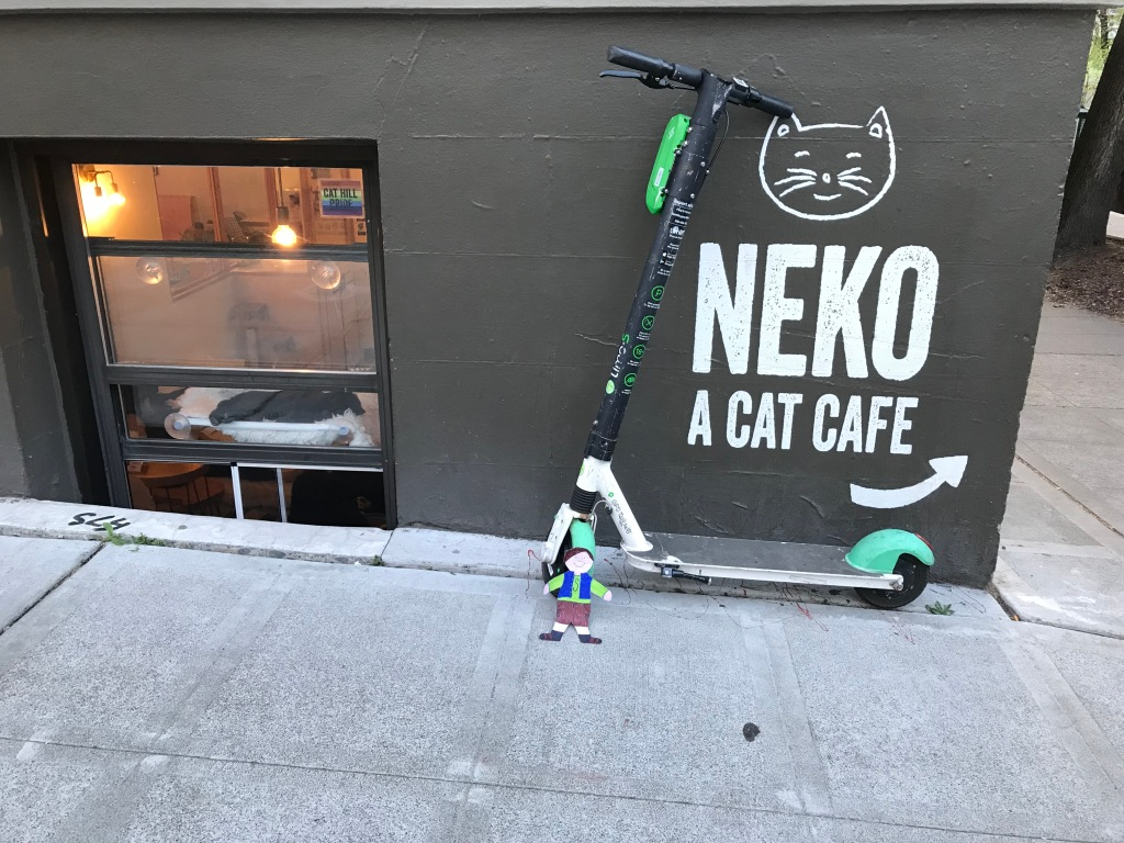 "Paper cut out of boy in front of scooter next to a sign reading ""Neko A Cat Cafe"" with cat lounging in window."
