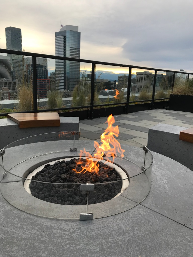 Fire in circular fire pit on roof of tall building, other skyscrapers in the background.