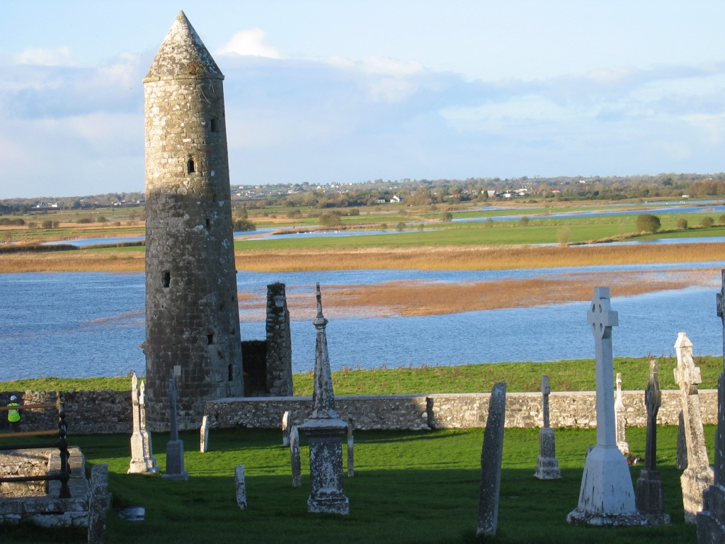 Old stone tower  in cemetery, Celtic crosses, River Shannon in distance.
