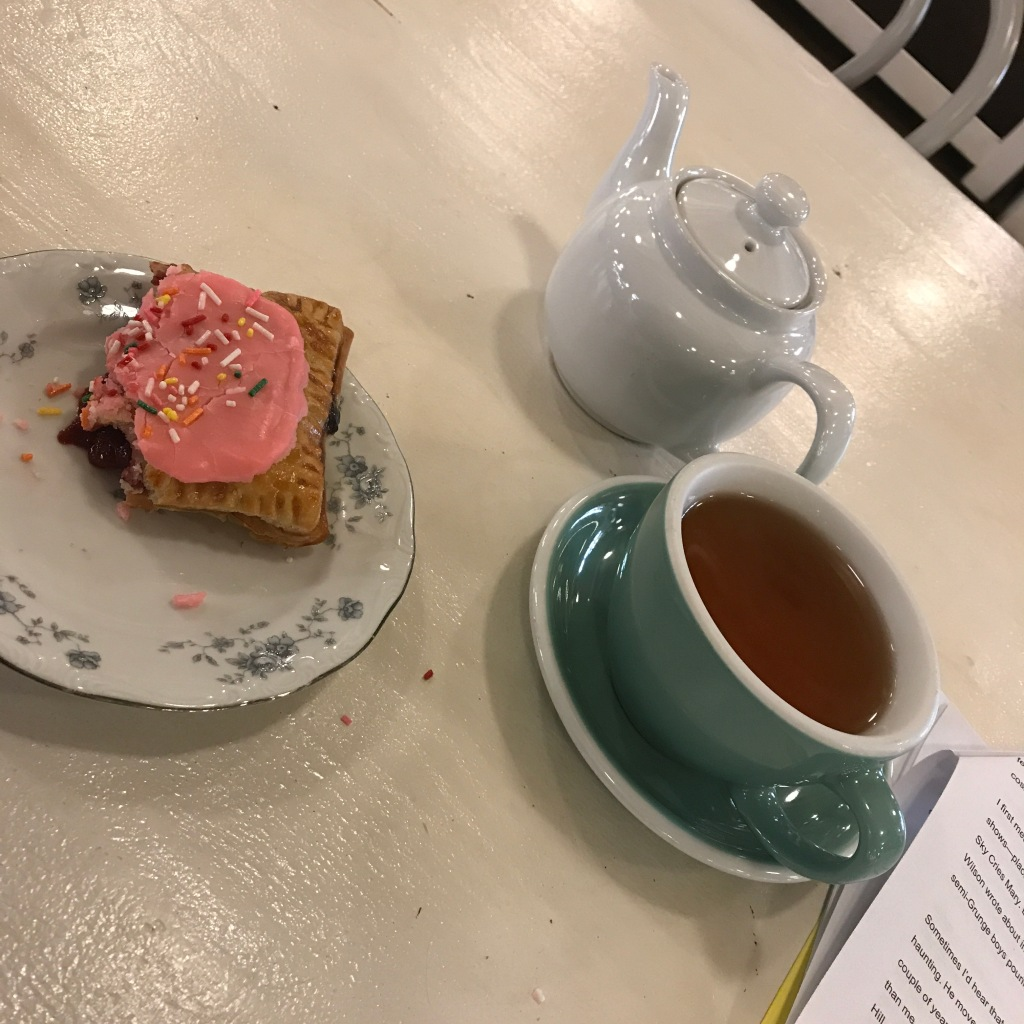 Teapot, full teacup, pastry on a flowered plate.