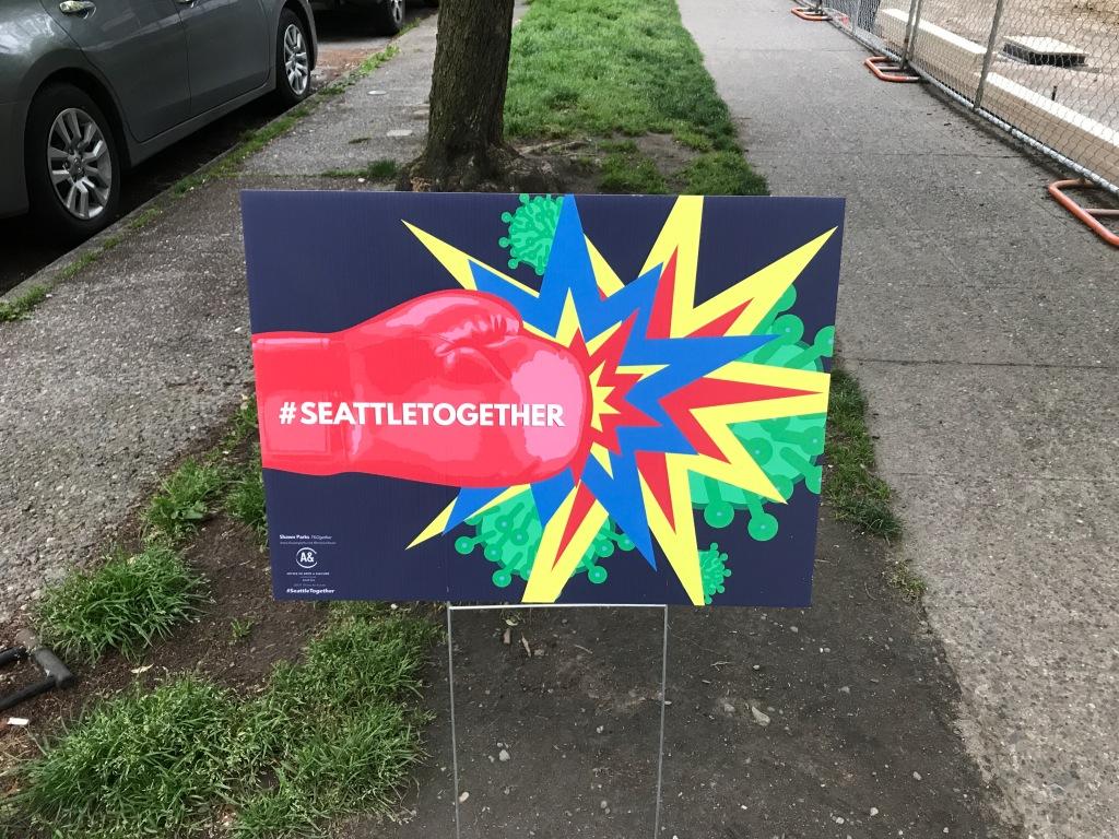 Sign on city street of red boxing glove punching Corona virus.
